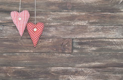 Vintage Red Hearts Hanging over Brown Wooden Background stock photo