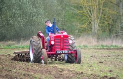 Vintage red International 1960`s  tractor ploughing field. ST NEOTS, CAMBRIDGESHIRE, ENGLAND - MARCH 19, 2017: Vintage red International 1960`s  tractor Royalty Free Stock Photography