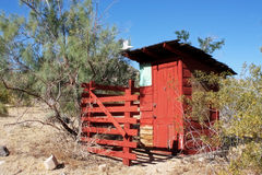 Vintage Red Outhouse in The Desert. A bright red vintage outhouse under blue skies on a sunny day in the desert royalty free stock photography