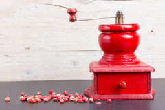 Vintage, red pepper mill with peppercorns Royalty Free Stock Images