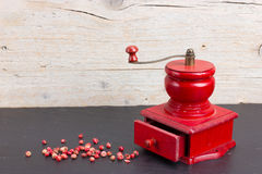 Vintage, red pepper mill with peppercorns Stock Photos