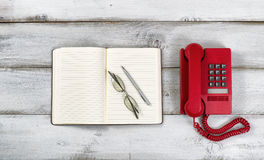 Vintage red phone and notepad with pen and reading glasses on ru Stock Photo