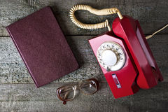 Vintage red phone, old glasses and notebook Stock Image