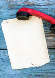 Vintage red phone and a piece of paper to write Royalty Free Stock Photos