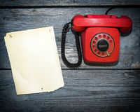 Vintage red phone and a piece of paper to write Royalty Free Stock Images