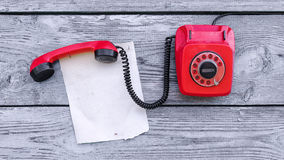 Vintage red phone and a piece of paper Stock Photo