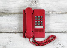 Vintage red phone on rustic white wooden boards Royalty Free Stock Photography