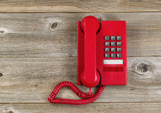 Vintage red phone on rustic wooden boards Stock Photography