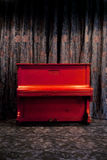 Vintage red piano. In dark theater or nightclub interior over floral decorated curtains background Royalty Free Stock Photo