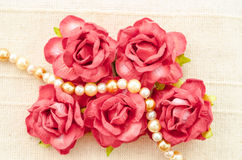 Vintage red roses and pearl necklace. Vintage red roses and pearl necklace on fabric background Stock Image