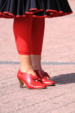 Vintage red shoes. Beautiful female legs with red shoes standing on the street Stock Photo