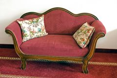 Vintage red sofa. An old sofa with two cushions standing on a red carpet against a white wall Stock Image