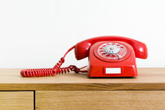 Vintage red telephone. On wooden desk Royalty Free Stock Image