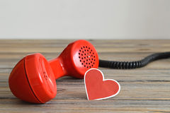 Vintage red telephone handset and heart shaped tag Stock Images
