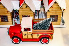 Vintage red toy pickup truck with Christmas lights and tree in back in front of a country Christmas village stock images