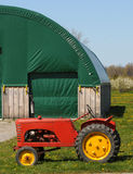 Vintage red tractor at a barn Royalty Free Stock Photography