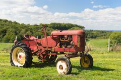 Vintage red tractor in landscape stock photography