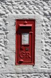 Vintage red UK postbox set in a white wall. An old red UK postbox which is still in use, set in a white painted old flint wall Stock Photography