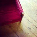 Vintage red velvet armchair on wooden floor Stock Photography
