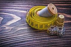 Vintage reel of thread measuring tape thimble spools on wooden b Stock Photos