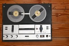 Vintage reel to reel tape recorder on a wooden background.Retro tape recorder from the USSR. Vintage reel to reel tape recorder on a brown wooden background stock image