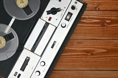 Vintage reel to reel tape recorder on a wooden background.Retro tape recorder from the USSR. Vintage reel to reel tape recorder on a brown wooden background royalty free stock photo