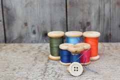 Vintage reels of thread and needle and button. Sewing tools Royalty Free Stock Photo