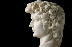 Vintage Replica of David. 's head in marble over a black background Stock Photo