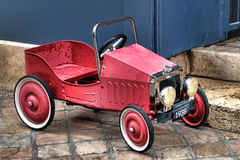 Vintage Reproduction French Pedal Red Toy Car. Vintage reproduction 1938 French pedal toy car with faded red paint and big retro headlights on an old cobblestone stock photos