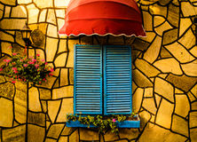Vintage Restaurant Window With Colorful Shutters And Umbrella. Inviting vintage restaurant decoration details on the outside of a building with colorful shutters Stock Photo