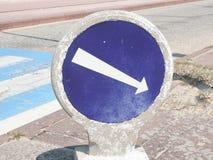 Vintage White arrow on blue traffic sign on street road. Vintage retro ancient White arrow on blue traffic sign on street road stock photos