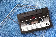 Vintage retro audio cassette on the background of blue jeans, close-up. Media technologies of the past 80-ies. Conceptual picture royalty free stock photos