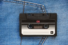 Vintage retro audio cassette on the background of blue jeans, close-up. Media technologies of the past 80-ies. Conceptual picture stock images