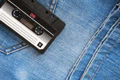 Vintage retro audio cassette on the background of blue jeans, close-up. Media technologies of the past 80-ies. Conceptual picture royalty free stock images