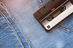 Vintage retro audio cassette on the background of blue jeans, close-up. Media technologies of the past 80-ies. Conceptual picture stock image