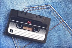 Vintage retro audio cassette on the background of blue jeans, close-up. Media technologies of the past 80-ies. Conceptual picture royalty free stock photo