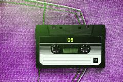 Vintage retro audio cassette on pink jeans background, close-up. Media technologies of the past 80-ies. Conceptual picture to stock photo