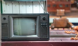 Vintage retro black and white color tv on wooden table with copy space stock photos