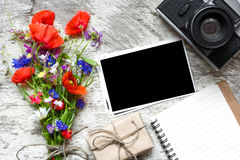 Vintage retro camera with blank photo frame and wildflowers bouquet with lined notebook and gift box. Top view. mock up Royalty Free Stock Photography