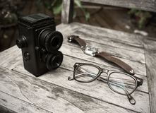 Vintage retro camera, eyeglasses and watch on wooden background Royalty Free Stock Photography