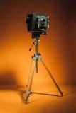 Vintage retro camera on a tripod. Vintage retro photo camera on a tripod on orange background Stock Photography
