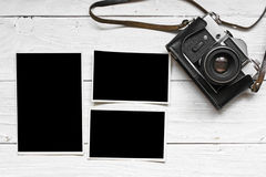 Vintage retro camera on wood table background with blank photos Royalty Free Stock Photography