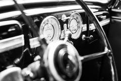 Vintage retro car interior, steering wheel, dashboard, black and white, closeup stock photo