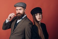 Vintage retro couple on red wall. Old style hat on bearded man and black fashion cap on beauty woman. Vintage retro couple on red wall. Old style hat on bearded stock images