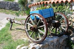 Vintage retro dilapidated part of wooden horse carriage with metal wheel frames used as garden decoration for planting flowers in. Vintage retro cracked stock photography
