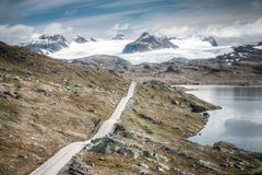 Vintage retro effect filtered hipster style travel image of mountain road leading to spectacular glaciers and lakes. royalty free stock photography