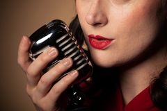 Vintage retro female singer with microphone royalty free stock photo