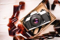 Vintage film camera in a wooden box on wooden white background with film Royalty Free Stock Images