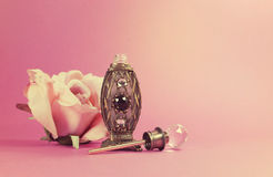 Vintage retro filter perfume bottle with crystal stopper and silk rose Stock Photos
