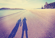 Vintage retro filtered picture of couple's shadow on beach Stock Photos